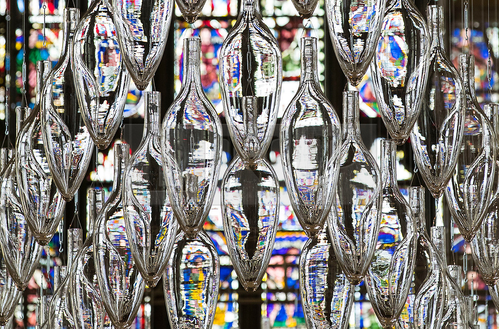 © Licensed to London News Pictures. 24/05/2018. Canterbury, UK. A sculpture entitled 'Boat of Remembrance, 2018' - a 20-metre installation of 100 glass amphorae - is suspended in the shape of a ship high above the Nave of Canterbury Cathedral. A series of  glass installations by artists Philip Baldwin and Monica Guggisberg reflecting on themes of war and remembrance, migration and refugees are going on display at the cathedral commemorating the 100th anniversary of the end of the First World War. Under an Equal Sky will take visitors on a journey that begins with the Boat of Remembrance in the Nave and ends with a glass wall of multi-coloured vessels in The Crypt . Photo credit: Peter Macdiarmid/LNP