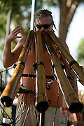 "Member of the band ""Emdee"" playing a set of didgeridoos at Mindill Beach Market in Darwin."