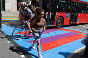 As a young cyclist pedals past, a woman crosses the multi-coloured markings of a crossing on Lower Regent Street, on 16th July 2021, in London, England.