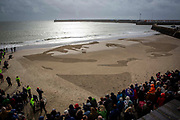 "The Poet & Soldier Wilfred Owen's face drawn on the beach in Folkestone as part of Danny Boyle's 'Pages of the Sea""  Armistice Day event commemorating 100 years since the end of the First World War on remembrance day the 11th of November 2018. Sunny Sands beach, Folkestone, Kent, United Kingdom."