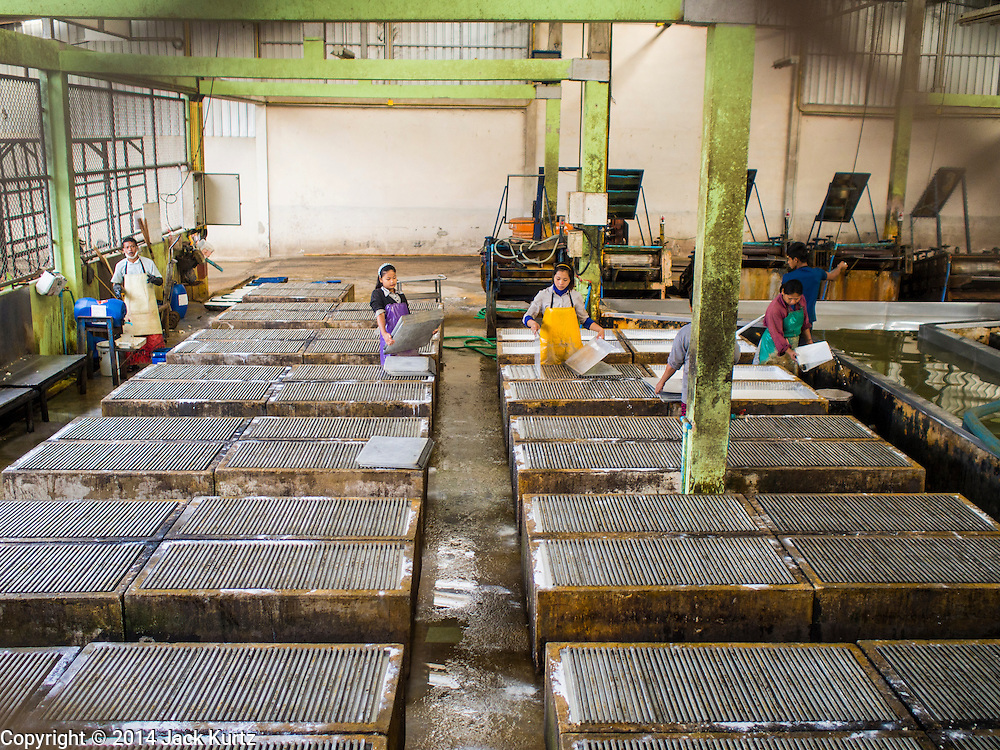 """16 DECEMBER 2014 - CHUM SAENG, RAYONG, THAILAND: Workers make rubber sheets at a large rubber plantation near Chum Saeng, Thailand. Thailand is the second leading rubber exporter in the world. In the last two years, the price paid to rubber farmers has plunged from approximately 190 Baht per kilo (about $6.10 US) to 45 Baht per kilo (about $1.20 US). It costs about 65 Baht per kilo to produce rubber ($2.05 US). Prices have plunged 5 percent since September, when rubber was about 52Baht per kilo. Some rubber farmers have taken jobs in the construction trade or in Bangkok to provide for their families during the slump. The Thai government recently announced a """"Rubber Fund"""" to assist small farm owners but said prices won't rebound until production is cut and world demand for rubber picks up.    PHOTO BY JACK KURTZ"""