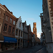 The Belfry of Bruges catches the early morning sun in the distance, behind a cobblestone street still cast in shadow in the historic center of Bruges, Belgium.