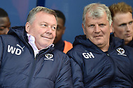 A playful look from AFC Wimbledon manager Wally Downes to his assistant Glyn Hodges during the EFL Sky Bet League 1 match between Oxford United and AFC Wimbledon at the Kassam Stadium, Oxford, England on 13 April 2019.