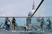 With the dome of St Paul's cathedral in the distance, pedestrians cross the river Thames on the Millennium Bridge, on 24th June 2021, in London, England. London's newest river crossing for 100-plus years coincided with the Millennium. It was hurriedly finished and opened to the public on 10 June 2000 when an estimated 100,000 people crossed it to discover the structure oscillated so much that it was forced to close 2 days later. Over the next 18 months designers added dampeners to stop its wobble but it already symbolised what was embarrassing and failing in British pride. Now the British Standard code of bridge loading has been updated to cover the swaying phenomenon, referred to as 'Synchronous Lateral Excitation'. (Photo by Richard Baker / In Pictures via Getty Images) CREDIT RICHARD BAKER.