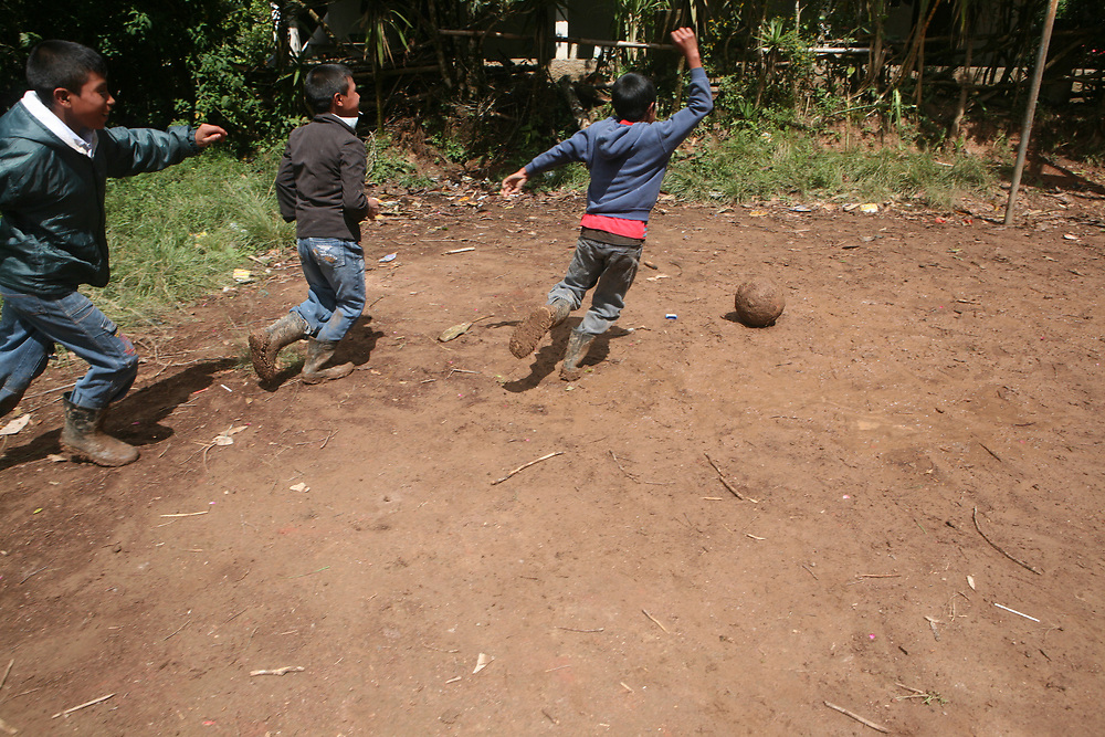 Boys play football in muddy wellington books in Chiquimula, Guatemala.
