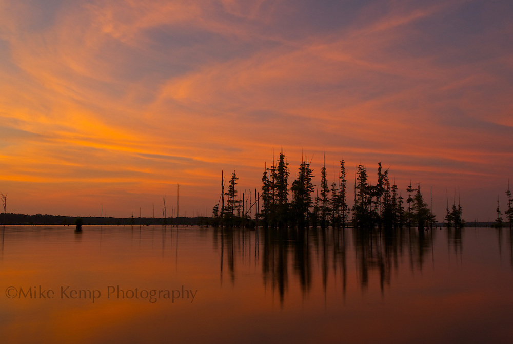 Trees are silhouetted against a colorful sky over Lake Conway near Mayflower, AR.