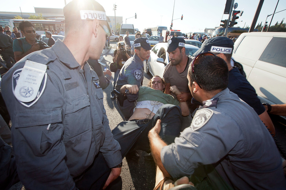 """Israeli police arrest a right wing Jewish activist during clashes in front of Israel's Supreme Court during a demonstration against the arrest of Kiryat Arba Chief Rabbi Dov Lior in Jerusalem on June 27, 2011. Rabbi Lior was arrested earlier today for refusing to appear for questioning on his endorsement of the content of the book """"Torat Hamelech"""" (The King's Torah), which discusses the rules of war, and states that in certain situations, non-Jews can be killed."""