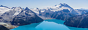 From Panorama Ridge, admire the vibrant turquoise color of Garibaldi Lake, which comes from glacial flour suspended in meltwater from Sphinx and Sentinel Glaciers. Above the lake rises Mount Garibaldi (2678 m or 8786 ft), a potentially active stratovolcano in Garibaldi Provincial Park, east of the Sea to Sky Highway (Route 99) between Squamish and Whistler, in the Coast Range, British Columbia, Canada. Below Mount Garibaldi are Table Mountain and Warren Glacier. Mount Garibaldi began erupting and growing steadily since 250,000 years ago and is the only major Pleistocene age volcano in North America known to have formed on top of a glacier. Although part of the Garibaldi Volcanic Belt within the Cascade Volcanic Arc, it is not considered part of the Cascade Range. The unusually-flat Table Mountain formed just 12,000 years ago from a lava eruption underneath a glacier! Regarding global warming and climate change: from the early 1700s to 2005, half (51%) of the glacial ice cover of Garibaldi Provincial Park melted away (reference: Koch et al. 2008, web.unbc.ca). The record of 1900s glacier fluctuations in Garibaldi Park is similar to that in southern Europe, South America, and New Zealand, suggesting a common, global climatic cause. This panorama was stitched from 3 overlapping images.