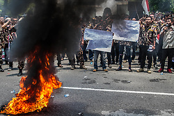 August 22, 2017 - Medan, North Sumatra, Indonesia - The protesters as slogans by burning tires during a demonstration outside the Malaysian Embassy in Medan on 22 August 2017, Indonesia. Dozens of people staged the protest accusing the Malaysian organizers of the Southeast Asian Games of negligence after the Indonesian flag was printed upside down in a souvenir guidebook. (Credit Image: © Ivan Damanik via ZUMA Wire)