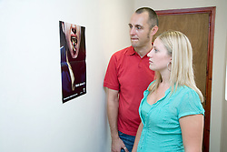 Two adults looking at an antismoking poster in a work corridor,