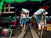 22 NOVEMBER 2017 - YANGON, MYANMAR: Stevedores unload a shipment of rice from a barge docked on the Twante Canal in Yangon. Myanmar's road system lags behind its neighbors in Southeast Asia and a lot of cargo is still moved by ships and barges. From here, export quality rice will be repackaged and shipped overseas and rice for domestic consumption will be shipped to other cities in Myanmar.    PHOTO BY JACK KURTZ