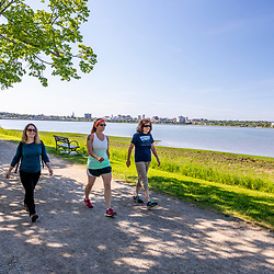 Three women walking on the Back Cove Trail next to Back Cove in Portland, Maine.