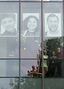 """Photogrpahers Jessica Wu (L) Mikayla Meadows (C) and Aaron Baker are seen beneath portraits of Skyview students in the windows of the Vancouver Library Thursday  May 17, 2018. Skyview photography students created the public art project called  """"Inside Out""""  The portraits will dominate the streetscape outside the library for a month. (Photo by Natalie Behring for the Columbian)"""