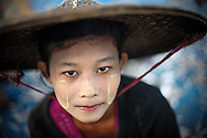 Myanmar, Ngapali. Portrait of a girl who wears thanaka on her face.<br />  Every single morning all the fisherman from the little village at Ngapali Beach come back home with their night catch. At the beach all the women wait for them and afterwards work with drying and selling fish and other creatures from the sea begins.