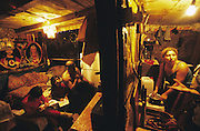 Roma living in a ramshackle hovel perched on an island on a river delta. Their village has literally been washed away several times. But the people return and rebuild their homes, they have nowhere else to go. Hermanovice, Slovakia 2004.