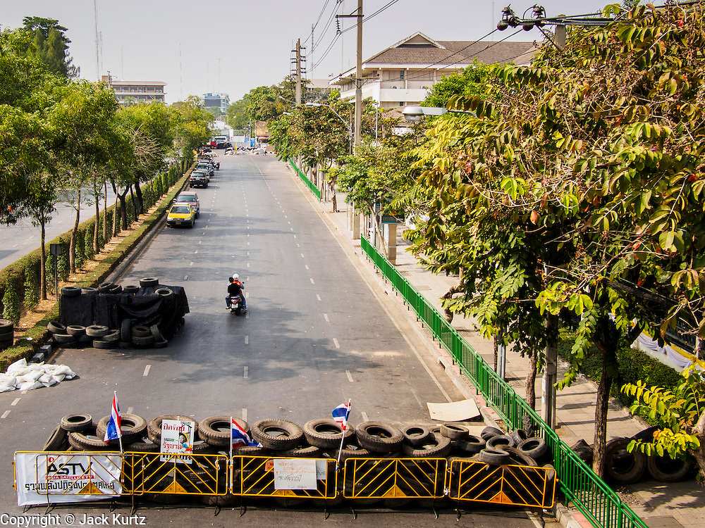 """30 DECEMBER 2013 - BANGKOK, THAILAND:  Anti-government protestors have put a roadblock across Phitsanulok Road near Government House in Bangkok. Violence around the anti-government protest sites has escalated in recent days and several protestors have been hurt by small explosive devices thrown at their guard posts. As a result, protestors are fortifying their positions with sandbags and bunkers. Suthep Thaugsuban, the leader of the anti-government protests in Bangkok, has called for a new series of massive protests after the 1st of the year and said it the shutdown, or what he described was the seizure of the capital, would be the day when """"People's Revolution"""" would """"begin to end and uproot the Thaksin regime.""""         PHOTO BY JACK KURTZ"""