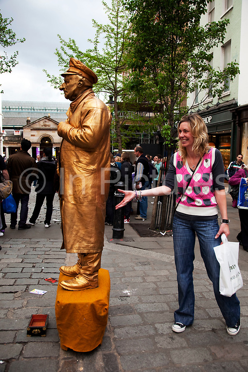 Tourists jokes to her friends with a gold statue like street performer stands still for hours. Covent Garden in the West End of London.