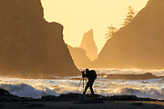 Photographer photographs sunset from Rialto Beach, Olympic National Park.