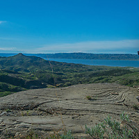 A hiker stands beside eroded rock features overlooking Fort Peck Reservoir in Charles M. Russell National Wildlife Reserve, Montana.