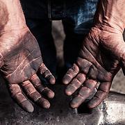 Die rußgeschwärzten Hände eines Messerschmieds über dem Amboss, Garmisch-Partenkirchen, Bayern, Deutschland.