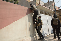Licensed to London News Pictures. 13/02/2017. Mosul, Iraq. Iraqi National Security Service officers watch as a colleague is boosted over a wall and into the garden of a suspected ISIS member in eastern Mosul.<br /> <br /> The Jihaz Al-Amin Al-Watani, roughly translated as the National Security Service or NSS, are a secretive Iraqi agency that works under the responsibility of the Ministry of Interior. Since the liberation of eastern Mosul in January 2017 the NSS have been actively hunting down ISIS members who stayed behind to continue terrorism as part of sleeper cells and residents who worked with the group during its two year occupation. Recruiting from across the country agency is responsible for internal security inside Iraq and has a broad remit to investigate and arrest everything from terrorists and foreign spies to financial criminals and drug traffickers. Photo credit: Matt Cetti-Roberts/LNP