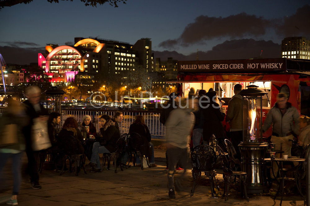 People stop at a mulled wine and hot cider stall along the riverside walkway as dusk turns to evening on the Southbank, London, United Kingdom. The South Bank is a significant arts and entertainment district, and home to an endless list of activities for Londoners, visitors and tourists alike.