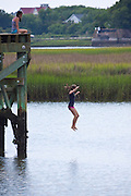 Young girls jump from a platform into Charleston Harbor on a warm summer day.