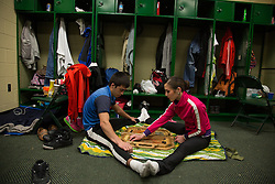 """Members of The Thundering Cossack Warriors stretch while playing a game in there dressing room before their performance. <br /> Ringling Bros. and Barnum & Bailey Circus started in 1919 when the circus created by James Anthony Bailey and P. T. Barnum merged with the Ringling Brothers Circus. Currently, the circus maintains two circus train-based shows, the Blue Tour and the Red Tour, as well as the truck-based Gold Tour. Each train is a mile long with roughly 60 cars: 40 passenger cars and 20 freight. Each train presents a different """"edition"""" of the show, using a numbering scheme that dates back to circus origins in 1871 — the first year of P.T. Barnum's show."""