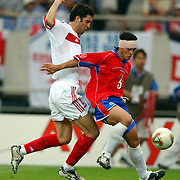 Costa Rica's Giolberto Martinez holds off Turkey's Hakan Sukur