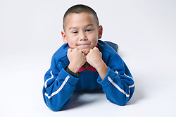 Young boy resting his head in his hands and lying on his front smiling,