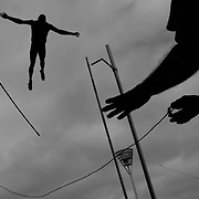 An official holds onto a support rope as a competitor fails at his pole vault attempt during a windy Australian National Athletics Championships at Sydney Olympics Park, Australia