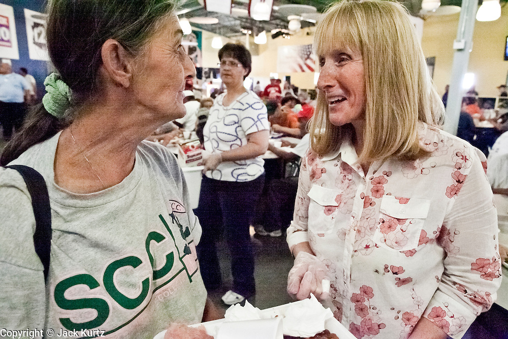 """Sept. 27 - PHOENIX, AZ: JACKIE, (left) a diner at the St. Vincent de Paul lunch service, talks to CAROL PICCO, a volunteer, after lunch Monday, Sept. 27. September 27, 2010 is the 350th Feast Day of Saint Vincent de Paul, also known as the """"Apostle of Charity."""" To mark the day, the Society of St. Vincent de Paul in Phoenix served birthday cake during the lunch service. The US Census office recently announced that poverty in the US has spiked to 14.3% of the population, the highest poverty rate since 1994. Officials at St. Vincent de Paul in Phoenix said that demand for their services have increased steadily in the last three years. They currently feed about 1,100 people, either homeless or members of the working poor, every day.    Photo by Jack Kurtz"""