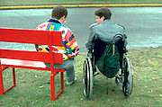 Couple age 30 resting in wheelchair at the MN State Fair.  St Paul  Minnesota USA