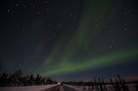 Northern Lights above backroad and lake in Kiruna, Swedish Lapland