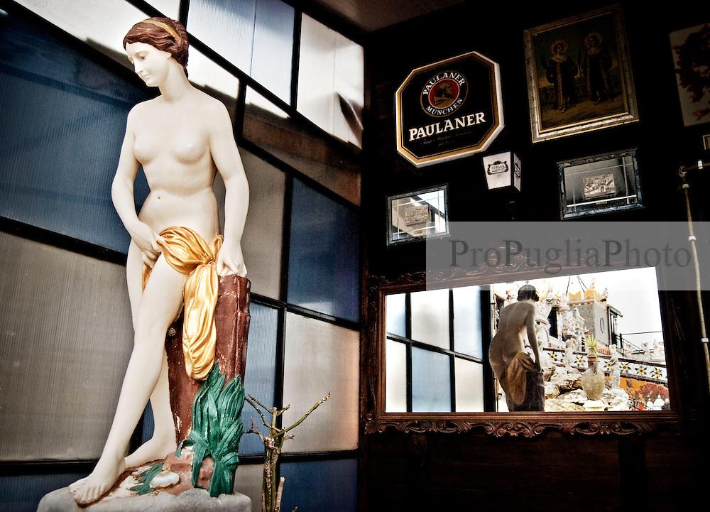 """Una scultura nel cortile di """"Vincent City"""", residenza del pittore salentino """"Vincent Brunetti""""nei pressi di Guagnano in provincia di Lecce. 29/03/2009 (PH Gabriele Spedicato) ..VINCENT BRUNETTI.Affettuosamente identificato con l'appellativo """"LA LIBELLULA DEL SUD"""", Vincent Brunetti è oggi considerato uno dei personaggi più emblematici della vita artistica meridionale..Nato a Guagnano di Lecce il 3 dicembre 1950 e residente a Milano da oltre vent'anni dove per i meriti artistici (egli è infatti pittore e scultore) gli è stato conferito nel 1970 l'AMBROGINO D'ORO. Fu colpito in tenera età dal virus della poliomelite. Gli effetti devastanti della malattia a seguito di due delicati interventi al piede sinistro lo stavano portando ad una quasi totale immobilità..Comincia comunque a dipingere e consegue, con il massimo dei voti, il diploma alla Scuola d'arte di Lecce..Dopo essere stato a Torino, si trasferisce a soli venticinque anni a Milano dove riceve numerosi riconoscimenti ed entra in contatto con elementi di spicco della scena artistica milanese come Francesco Messina (sotto la cui guida frequenta l'Accademia di Brera); Giacomo Manzù che lo segue ed incoraggia nel corso della sua attività; Arnaldo Pomodoro che lo accoglie presso la sua Bottega..Sempre a Milano, egli collabora con l'attrice Paola Borboni ed il poeta Bruno Villar alla realizzazione di numerose attività culturali e di diversi programmi televisivi..Con il passare degli anni egli è sempre più debilitato dalla malattia..Grazie alla geniale scoperta di Mariano Orrico, ideatore """"Lamina Bior"""" secondo il quale, ogni genere di malattia può essere sconfitta con il proncipio dell'elettricità statica, Vincent Brunetti ha potuto recuperare in pieno la sua vitalità e gioia di vivere..Nella sua """"DANZA"""" propiziatoria è espresso in pieno il bisogno di LIBERTA' che è nascosto nel cuore di ogni uomo e nel suo """"VOLO"""" il desiderio di liberarsi dal peso della materia..Nell'elasticità delle articolazioni rese forte e robuste"""