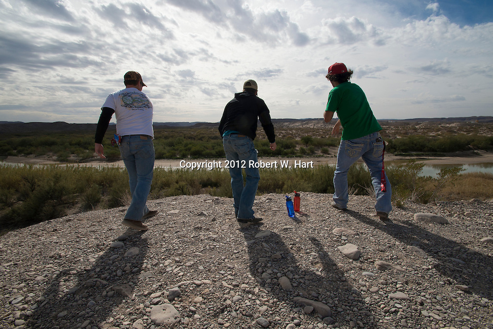 Geology students from the University of Central Oklahoma, in Edmund, Ok., attempt to throw rocks into the Rio Grande River in Big Bend National Park on December 21, 2012. Boquillas del Carmen in Coahuila, Mexico is visible in the distance. The new Customs and Border Patrol crossing and point of entry in Rio Grande Village will open on January 28, 2012..Photographer: Robert W. Hart