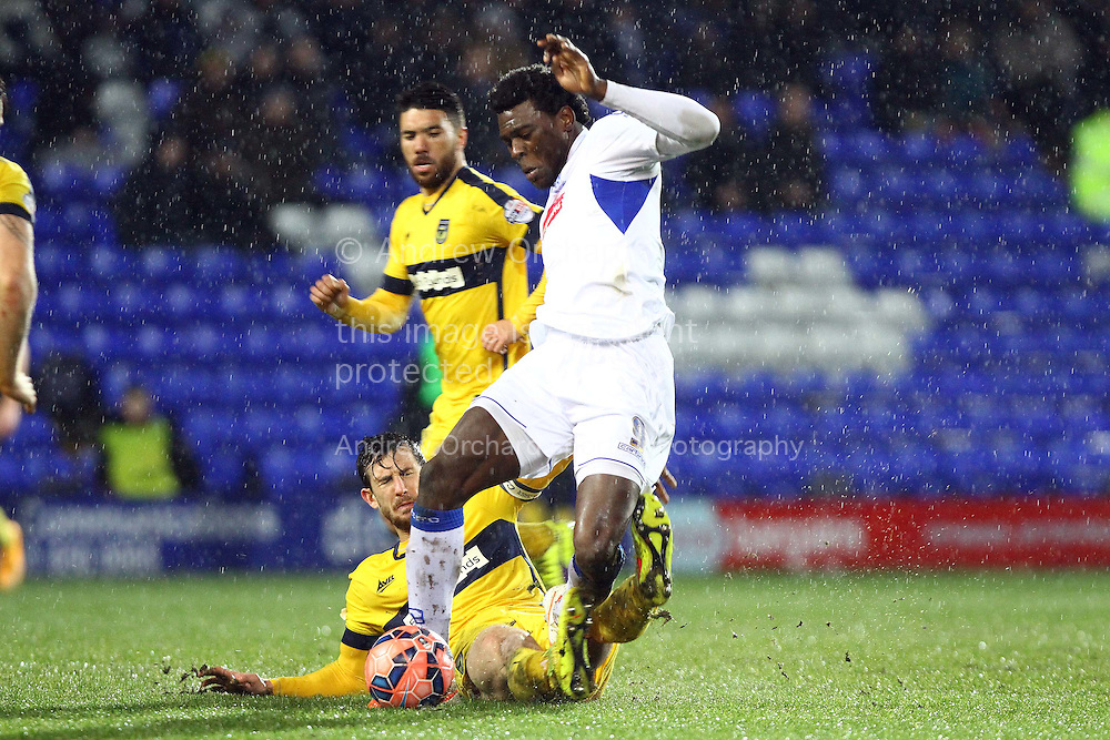 Jake Wright of Oxford United tackles Kayode Odejayi of Tranmere Rovers (c). The FA Cup, 2nd round replay, Tranmere Rovers v Oxford United at Prenton Park in Birkenhead, England on Tuesday 16th December 2014.<br /> pic by Chris Stading, Andrew Orchard sports photography.