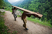 Two kids carrying a heavy log of wood on the dangerous path to Kheerganga. Pictures from the Parvati valley in Kullu, Himachal Pradesh, India