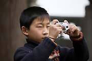 Boy takes a photograph at Summer Palace, Beijing. China has a one child family planning policy to limit population.