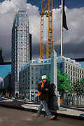 A construction worker walks past a hoarding showing the future skyscraper being built by housing developer Barratt at Blackfriars Circus at the southern end of Blackfriars Bridge Road, south London borough of Southwark.