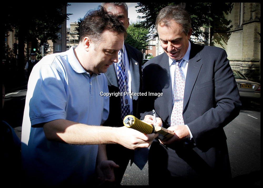 The Prime Minister Tony Blair signs a cricket bat for ?????? after the service at  All Saints Church,The Drive,Hove. PRESS ASSOCIATION Photo. Photo Credit should read:Andrew Parsons/PA