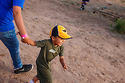 """12 JULY 2012 - FT DEFIANCE, AZ: A boy plays behind the worship tent at the 23rd annual Navajo Nation Camp Meeting in Ft. Defiance, north of Window Rock, AZ, on the Navajo reservation. Preachers from across the Navajo Nation, and the western US, come to Navajo Nation Camp Meeting to preach an evangelical form of Christianity. Evangelical Christians make up a growing part of the reservation - there are now more than a hundred camp meetings and tent revivals on the reservation every year. The camp meeting in Ft. Defiance draws nearly 200 people each night of its six day run. Many of the attendees convert to evangelical Christianity from traditional Navajo beliefs, Catholicism or Mormonism. """"Camp meetings"""" are a form of Protestant Christian religious services originating in Britain and once common in rural parts of the United States. People would travel a great distance to a particular site to camp out, listen to itinerant preachers, and pray. This suited the rural life, before cars and highways were common, because rural areas often lacked traditional churches.  PHOTO BY JACK KURTZ"""