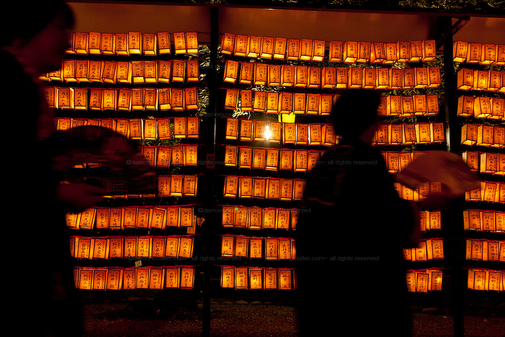Women holding fans walk past a wall of yellow lanterns, each containing the name of a fallen serviceman, during the Mitama matsuri in remembrance of Japan`s war dead at the controversial Yasukuni Shrine in Tokyo, Japan. Sunday, July 13th 2008