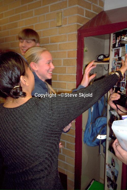 Students age 15 reaching into open locker.  Golden Valley Minnesota USA