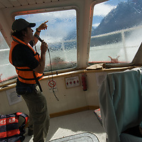 A tour guide entertains adventure travelers in a wave-tossed boat on Grey Lake in Torres del Paine National Park, Chile.