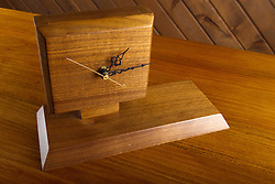 22 March 2014:   handmade wooden walnut clock without a face, just minute, hour, and second hand.  Displayed in front of a car sided wall on top of a wood desk.