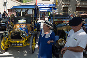 An elderly French couple and visiting vintage cars in a rural village, during a three-day rally journey through the Corbieres wine region, on 26th May, 2017, in Lagrasse, Languedoc-Rousillon, south of France. Lagrasse is listed as one of France's most beautiful villages and lies on the famous Route 20 wine route in the Basses-Corbieres region dating to the 13th century.