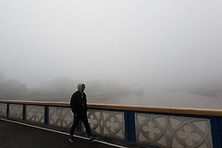 © Licensed to London News Pictures. 17/12/2016. LONDON, UK.  A man walks on Tower Bridge over the River Thames during foggy weather this morning. London and the River Thames was shrouded in thick fog this morning.  Photo credit: Vickie Flores/LNP