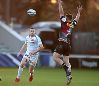 Finn Russell of Racing chips the ball over Will Evans of Harlequins