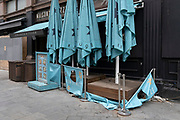 The torn and dirty parasols that once sheltered customers who used to eat outside a Lebanese restaurant business in Leicester Square, closed since the Coronavirus pandemic lockdowns when none other than essential shops closed, on 29th April 2021, in London, England.